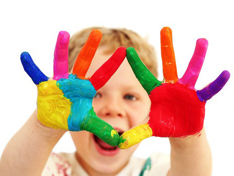 Five year old boy with hands painted in colorful paints ready for hand prints
